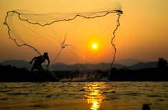 Light and shadow fishermen. Sunset Light and shadow fishermen Royalty Free Stock Images
