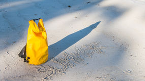Light and shadow on sandy beach with yellow waterproof bag and h Royalty Free Stock Photo