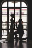 Silhouettes of a man in a suit and women in a dress and with a bouquet of flowers. A man dropped on one knee in front of royalty free stock images