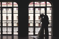 Silhouettes of a man in a suit and a woman in a dress and with a bouquet of flowers kissing and hugging each other near royalty free stock images