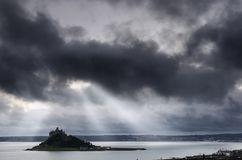 Light shafts over a somber St Michael`s mount. After a storm passed the dark cloud break up to allow beautiful light shafts to illuminate the sea around the Stock Photo