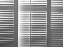 Light through shutters. Light pours through shutters in shuttered windows stock image