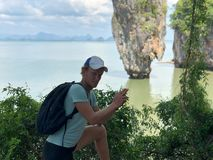 A light-skinned guy in a cap and a t-shirt with a backpack folded a gun from his fingers on picturesque James bond island in stock photography