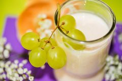 Light small health breakfast with grapes, milk, pastry and flowers Stock Photography