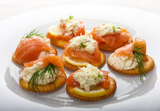 Light snack. From smoked salmon with soft cheese and herbs on crackers Royalty Free Stock Image