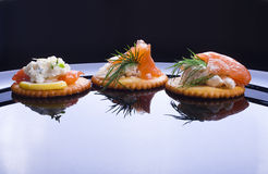 Light snack. From smoked salmon with soft cheese and herbs on crackers Royalty Free Stock Images