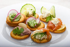 Light snack. From various ingredients with soft cheese and herbs on crackers Stock Image