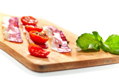 Light snack. Dried tomatoes and bacon served on board. Stock Photography