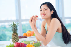 Light snack. Portrait of a happy girl having a healthy snack of fresh fruit and vegetables Royalty Free Stock Photos