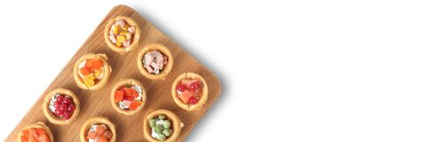 Free Light Snacks Or Tartlets On A Wooden Board On A White Background, Wide Banner, Flyer Or Banner Concept For Catering Or Food Stock Images - 215037114