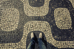 Light Sneakers shoes walking on Ipanema mosaic sidewalk top view Stock Images