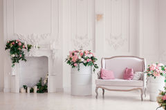Light sofa with pink pillows stands in the interior light studio room near the romantic fireplace decorated with spring. Flowers, wreath, candles Royalty Free Stock Photos