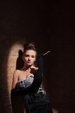 In the light of soffit. Elegant woman stands in the light of soffit and holds cigarette in the hand Royalty Free Stock Photography