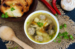 Light soup with dried mushrooms, meatballs and maccheroni in a white bowl. Royalty Free Stock Images