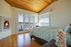 Light spacious bedroom with vaulted plank ceiling. royalty free stock photo