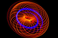 Light spiral, red and blue lines on a black background Stock Photos