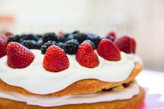 Light sponge cake with white icing and mixed berries strawberri Stock Images