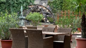 Light spring rain and wind on the cafe terrace. An outdoor fountain and many green plants. No People. stock video