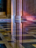 Light from stained glass windows on wall of church. Colorful light from a stained glass window in a cathedral falls on the polished marble of the church Stock Image