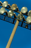 Light Standard Background. Light standard with flood lights at a stadium - with blue sky in the background - use as background Stock Image