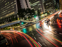 Light streaks from Traffic split between Tokyo office tower. Traffic streaks on either side of an office building in  Tokyo, Japan. Just having rained, the road Stock Image