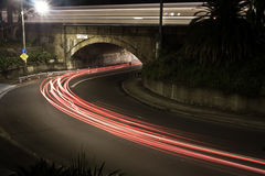 Light streaks under and over an old bridge. Royalty Free Stock Photography