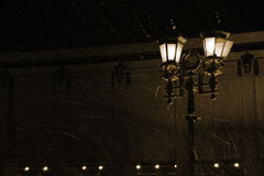 Light street lamp during a snow storm royalty free stock photography