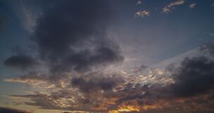 Light stretched clouds over evening sky, lake sunset skies time lapse shot. Sun disk behind dense stripe of clouds.