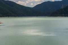 A river`s shiny green water & mountains royalty free stock photography