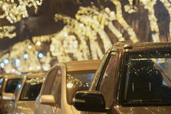 Light string decorated trees with cars at Christmas time Royalty Free Stock Images