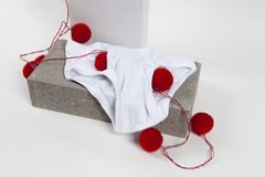 Light string y fronts white. A red pompon light string ine a y fronts underwear placed on a cinder block. White background. Minimal funny and quirky pop still Royalty Free Stock Image