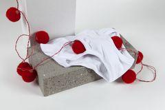 Light string y fronts white. A red pompon light string inside a y fronts underwear placed on a cinder block. White background. Minimal funny and quirky pop still Stock Image