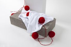 Light string y fronts white. A red pompon light string inside a y fronts underwear placed on a cinder block. White background. Minimal funny and quirky pop still Stock Photo