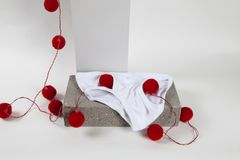 Light string y fronts white. A red pompon light string inside a y fronts underwear placed on a cinder block. White background. Minimal funny and quirky pop still Royalty Free Stock Photo
