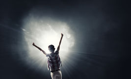 In light of success. Rear view of woman with hands up facing success Stock Images