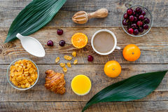 Light summer breakfast. Muesli, oranges, cherry, croissant and coffee on wooden table background top view Royalty Free Stock Image