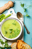 Light summer green pea cream soup in bowl with sprouts, bread toasts and spices Stock Photography