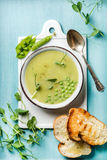 Light summer green pea cream soup in bowl with sprouts, bread toasts and spices Stock Photo