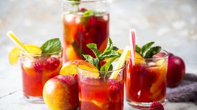 Alcohol cocktail for a summer party. Light summer refreshing drink with fruits and berries - sangria. In glasses on a gray table Stock Photography