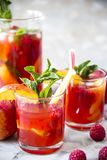 Alcohol cocktail for a summer party. Light summer refreshing drink with fruits and berries - sangria. In glasses on a gray table Stock Photo