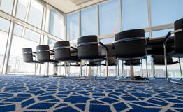 Light, sunny boardroom with bent tubular steel chairs and blue carpet with geometric pattern, at the Aga Khan Centre, London
