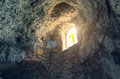 Light of sunshine stream through window with cross. Silhouette of the cross at the window in cave royalty free stock photography