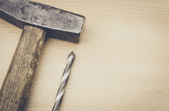 On a light surface hammer and drill. On a wooden surface hammer and drill Royalty Free Stock Image
