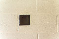 Light Switch. A black light switch on a cement block wall Royalty Free Stock Photo