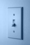 Light switch. Blue light switch on wall stock photos