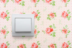 Light switch on floral wallpaper Stock Image