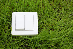 Light switch on a green grass background Stock Photos