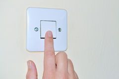 Light switch. A hand of a woman pressing a wall mounted light switch royalty free stock photo