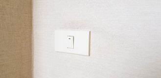 Light switch On/Off on brown wallpaper for open lighting inside the room or building royalty free stock photo