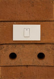 Light switch on red brick wall Stock Photo